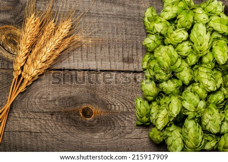 Hops and golden ripe wheat of cone on a old wooden table - stock photo