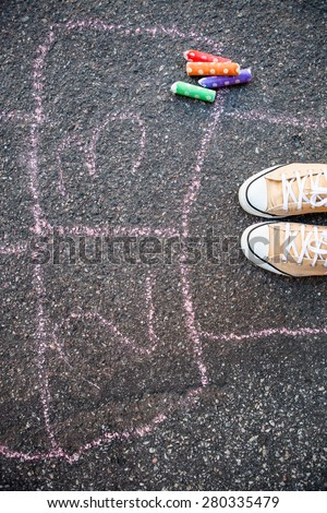 Hopschotch and colorful street chalk on asphalt - stock photo