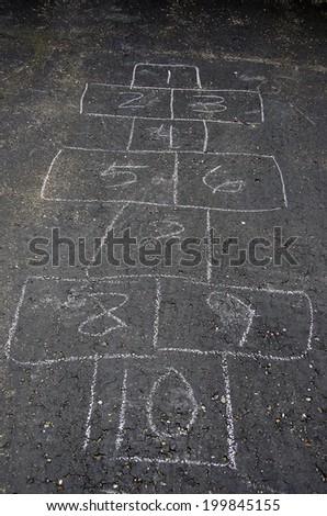 hopscotch game in chalk on asphalt - stock photo