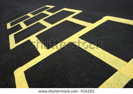 hopscotch jumping game at a school, yellow on black - stock photo