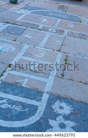 Hopscotch on an asphalt floor with chalk drawings of numbers and squares as an icon of youth innocence and children playing a fun jumping game at recess or after elementary school. - stock photo