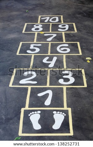 Hopscotch painted indelible ink on black asphalt for children outdoor. - stock photo