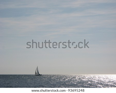 Horizon over the sea with a yacht sailing from right to left.