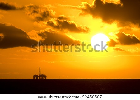 Horizon view of an oil rig in sunset time - stock photo