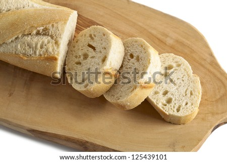 Horizontal and close up image of chopped French bread on a chopping board isolated on