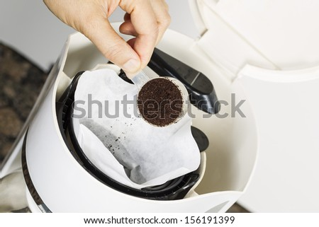 Horizontal angled photo of female hand putting fresh coffee grounds in white bleached coffee filter with coffee maker, and stone kitchen counter top in background