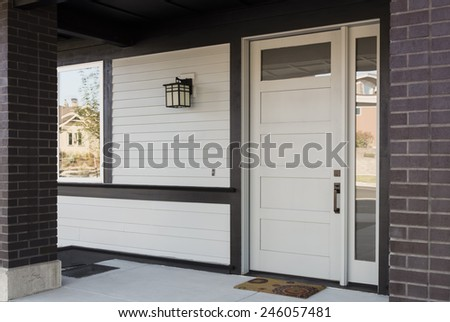 Horizontal Angled Shot of White And Black Front Entryway with White Siding, a White Front Door, and Black Framing - stock photo