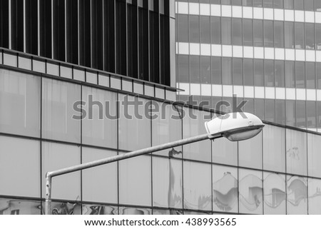 Horizontal background with building windows. Black and white architecture abstracts from office buildings and public lamp in front. - stock photo