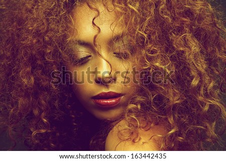 Horizontal beauty portrait of a young female fashion model with curly hair covering face - stock photo