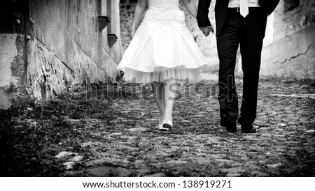 horizontal black & white image of bride & groom holding hands walking towards the camera - stock photo