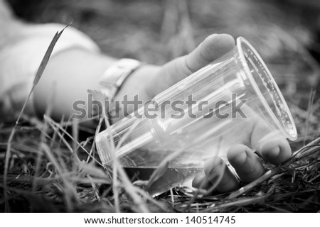 horizontal black & white image of drunken mans hand holding an empty glass - stock photo