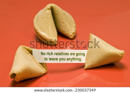 Horizontal broken fortune cookie saying 'No Rich Relatives Are Gonna Leave You Anything'. - stock photo