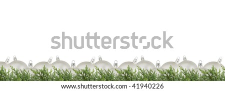 Horizontal Christmas border of silver balls and juniper on white.