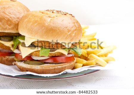 Horizontal close-up from front on juicy huge chicken scallop burger - stock photo