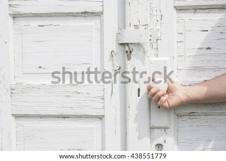 horizontal close up image of a caucasian man's hand opening a pure white rustic double door with white door knob. - stock photo
