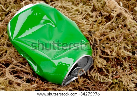 horizontal close up of a crushed green aluminum drink can on moss - stock photo