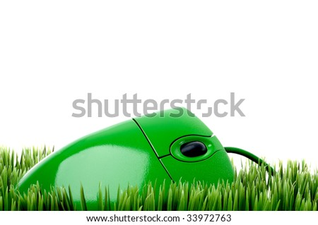 horizontal close up of a green computer mouse on grass - stock photo