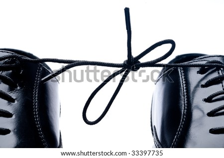 Horizontal close up of a pair of black leather business shoes with laces tied together - stock photo