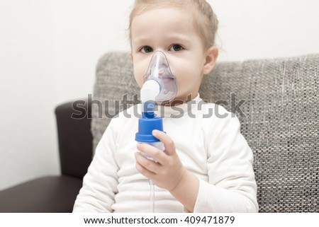 horizontal close up portrait of a little girl sitting on a gray couch holding an inhaler on her mouth and face  and looking serious on a white background - stock photo