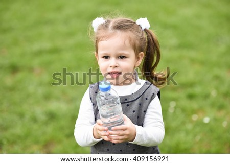 horizontal close up portrait of a little girl standing and holding a bottle of water on a sunny day in a park or playground with green grass in the background - stock photo