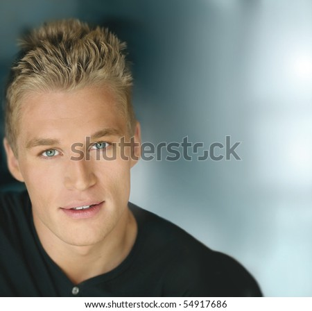 Horizontal close-up portrait of a smiling confident young male model with a futuristic modern background with lots of copy space - stock photo