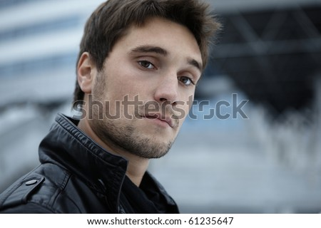 Horizontal close-up portrait of a smiling confident young male model with a futuristic modern background with free copy space - stock photo