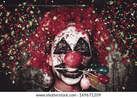 Horizontal close-up portrait on the face of a mad carnival clown holding balloon cake decoration in mouth under a fall of confetti. Celebrating Halloween - stock photo