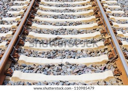 Horizontal closeup of railway lines in sunlight - stock photo