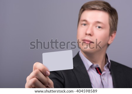 Horizontal closeup portrait of young attractive man in a jacket and shirt showing your business card or any other card. Neutral grey background - stock photo