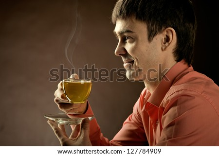 horizontal closeup portrait  the  beautiful man hold cup with green  tea,  on brown background