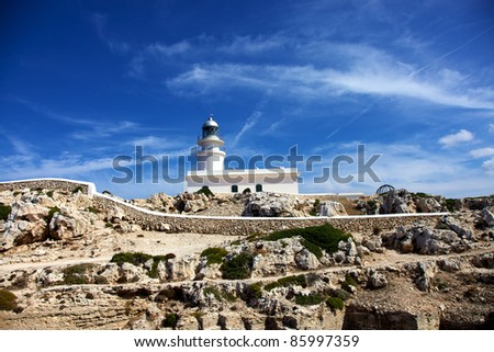 Horizontal color image of a white lighthouse in the distance. Rocks and plants in the bottom part of the image and a beautiful blue sky on top. - stock photo