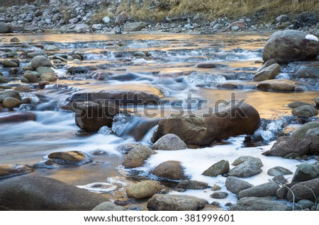 horizontal color image taken with very slow shutter speed to capture flowing water in a creek in Colorado in winter / Beautiful Colorado Creek in Winter - stock photo