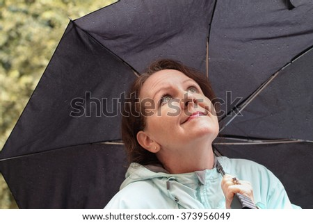 horizontal color image with a happy, smiling woman looking upward as she holds her black, rain covered, open umbrella outside / Looking Forward to a Change in Weather - stock photo