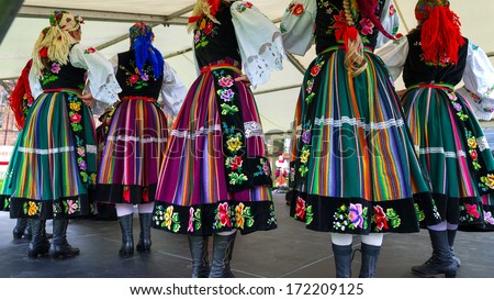 Horizontal colour image of female polish dancers in traditional folklore costumes on stage  - stock photo