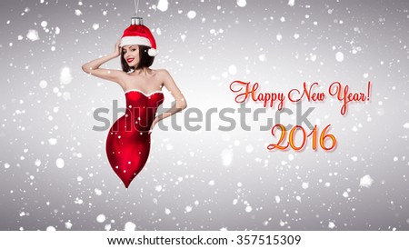 Horizontal composite shot of a beautiful girl as christmas tree decoration on a gray background wearing a christmas red hat with the snow falling behind her and a Happy New Year sign on the side - stock photo
