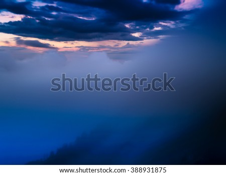 Horizontal dramatic clouds in mountains landscape backdrop