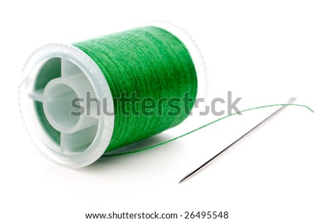 Horizontal extreme closeup of a spool of brown thread and a needle - stock photo