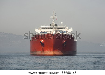 "Horizontal front view image of a red Ultra Large Crude Carrier, or ""Super Tanker.""  These vessels are capable of carrying up to two million barrels of oil across the seas. - stock photo"