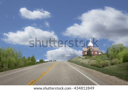 horizontal image of a beautiful ukrainian red brick church sitting on a hill beside a highway with a beautiful blue sky with white clouds floating by. - stock photo