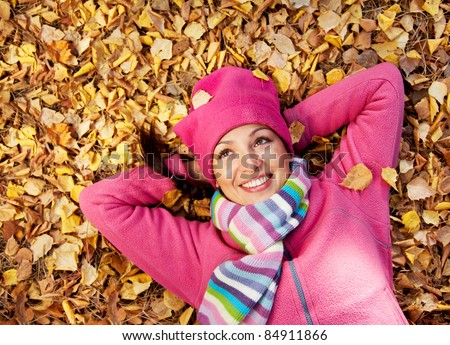 Horizontal image of a beautiful young woman lying in a pile of leaves. - stock photo