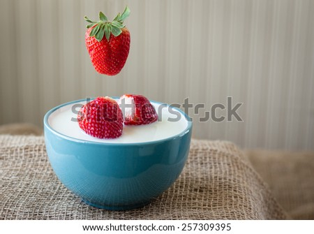 horizontal image of a blue glass bowl filled with milk and two strawberries floating in it with a strawberry suspended above the bowl on burlap background with room for text. - stock photo