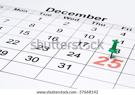 Horizontal image of a calendar with Christmas day marked with a green tack - stock photo