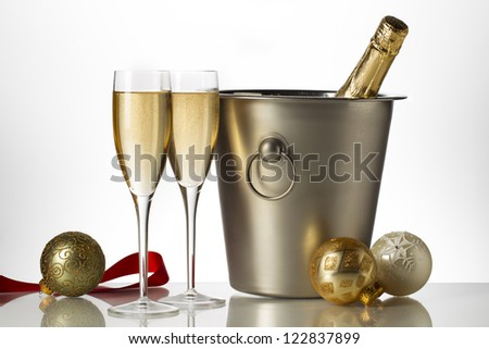 Horizontal image of a champagne bottle on an ice bucket with goblet on a holiday season - stock photo