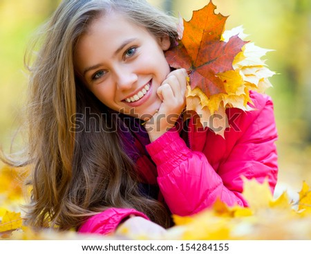Horizontal image of a cheerful girl lying in autumn leaves - stock photo