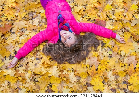 Horizontal image of a cheerful girl lying in autumn leaves
