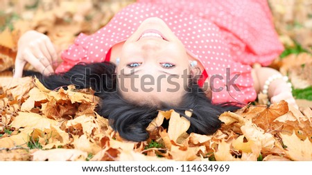 Horizontal image of a cheerful girl with blue eyes lying in autumn leaves - stock photo