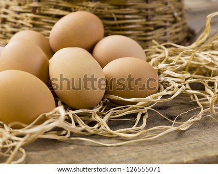 Horizontal image of a group of brown eggs on hay with a basket on the back - stock photo