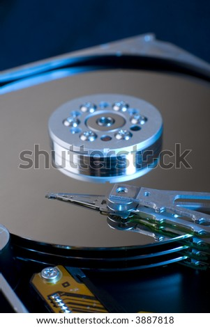 Horizontal image of a Hard Disk Drive, opened up, with blue side lighting.