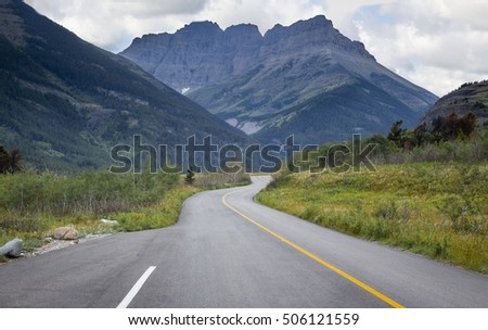 horizontal image of a highway winding its way through the mountains on a beautiful summer day.