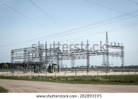 horizontal image of a large electric station structure sitting under a clear blue sky in the summer time. - stock photo
